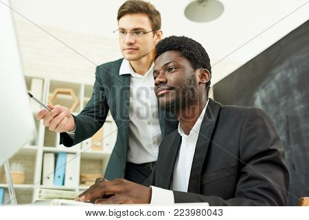 Low angle portrait of two businessmen, one of them African,  looking at computer screen  while discussing work project sitting at desk in modern office