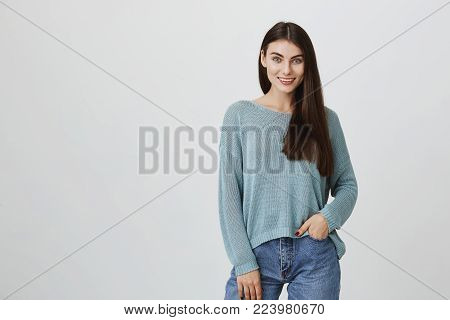 Positive student girl posing against gray background, looks with smile at camera, holds one hand in pocket of jeans. Horizontal shot of beautiful young woman with blue appealing eyes.