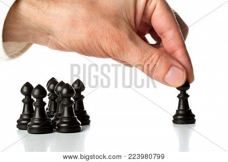 Business man moving chess figure in front of other chess figures - management, leadership, teamlead or strategy concept over white background