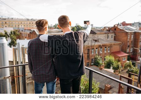 Selfie on a rooftop. Friends taking photo to share in social networks. Youth bff lifestyle