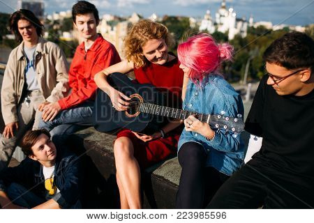 Girl giving guitar lessons to a friend. Playing musical instrument together. Free spirits lifestyle. Urban hipster teenagers leisure on a rooftop