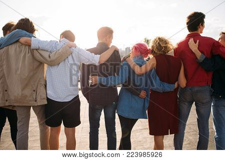 Back view of young diverse people group. Arm around. Unity support. Friendship together