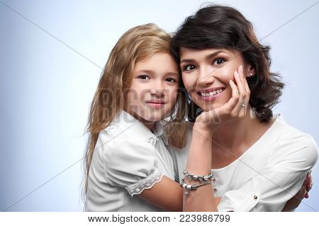 Family photo of a happy couple: smiling a mother and her beloved daughter. They are very pretty and nice. They were white t-shirts and hug each other. Portrait was made on a white studio background.