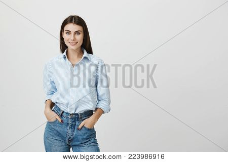 Photo of positive good-looking pleased student girl with dark hair in stylish shirt poses against studio wall with hands in pockets, wears denim clothes, being happy to receive praising words from parents for diligence