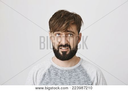 Indoor portrait of disappointed unsatisfied bearded european man looking at his messy hair with dislike, standing over gray background. Maybe I should finally call barber to make appointment.