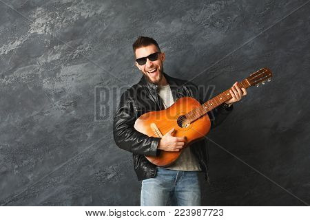 Happy stylish smiling man in sunglasses playing on guitar in studio. Hobby and musician concept. Fashion boy on grey background, copy space