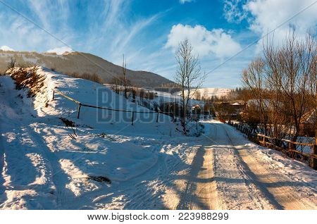 snowy road through the Podobovets village. beautiful winter rural scenery in afternoon