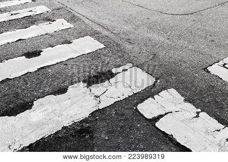 Pedestrian crossing road marking Zebra, white stripes over dark asphalt pavement, background photo texture