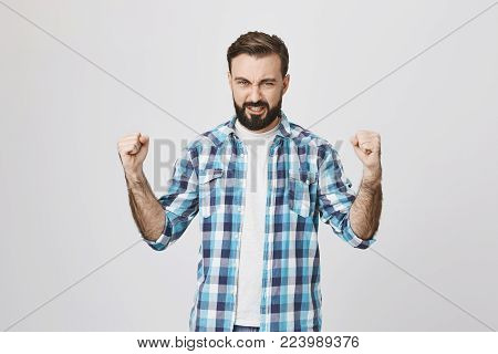 Portrait of handsome athletic adult male showing power and muscles while wearing plaid shirt, standing over gray background. Husband shows wife he can handle everything and fix shower on his own.