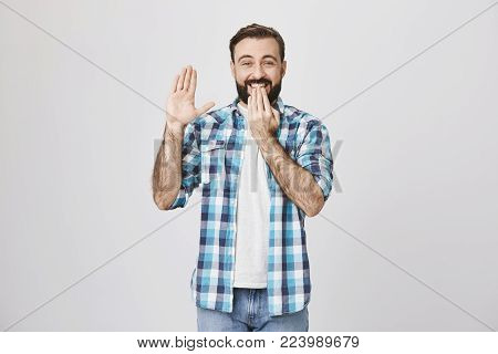 Portrait of funny laughing bearded guy holding hand near mouth and raising another, expressing his guilt, over gray background. Spouse confessed that it was him who left dirty plate in refrigerator.