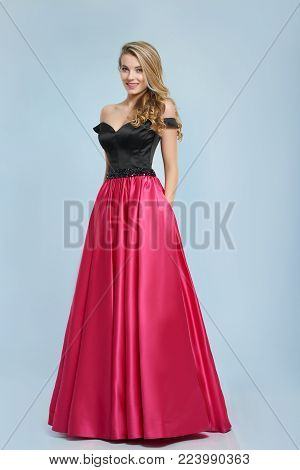 Beatiful girl with curly blonde hair stands in amazing evening dress, that was made in black and pink colores. she looks like a princess. Good choice for a prom evening.