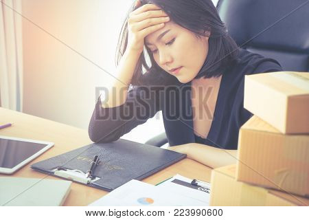 Tired Asian office woker with hand on her head getting headache