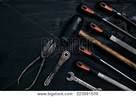 Series of many sharp steel blades and hammer on black wooden background. Set of chisels. Top view. Copy space. Still life. Flat lay