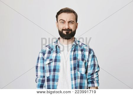 Portrait of funny disappointed bearded man, lifting his eyebrow and fake smiling while looking at camera, over gray background. Stomach rumbles during business meeting. Guy feels embarrassed. Advertisement concept