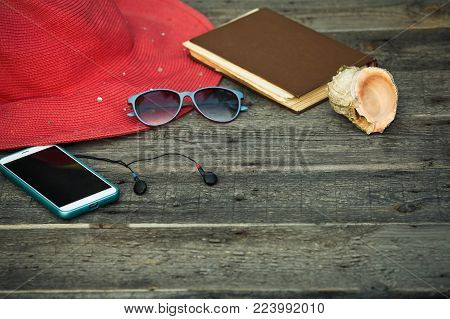 A hat, smartphone, a book as well of wooden background