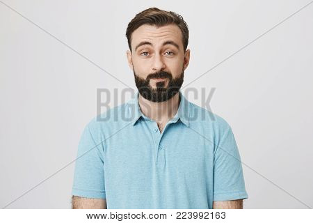 Portrait of attractive adult with beard and moustache expressing that he is not impressed, lifting his eyebrows and smiling, over gray background. Guy knows he hears lie but makes look he believes. Advertisement concept