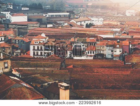 Black glass and metal trolley cable car slowly moving over long red tile roofs of old historical houses in Porto, Portugal; modern ropeway over historical district of European city