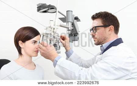 optometrist doing eyesight with woman patient measurement with optical phoropter isolated on white