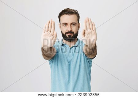 Studio shot of attractive young man with beard and stylish haircut stretching his palms at camera with calm expression, over gray background. Copy space