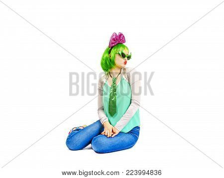 Beautiful young woman in an outrageous outfit spending time in the studio. Attractive Caucasian female model in fashion accessories and green wig, playfully posing