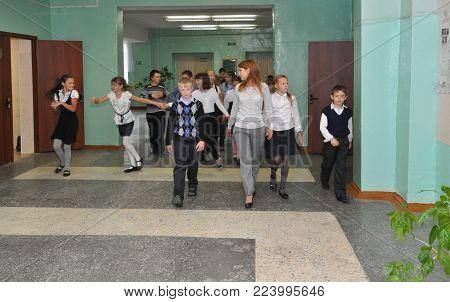 Gadjievo, Russia - September 19, 2012: The teacher walks with the children along the school corridor