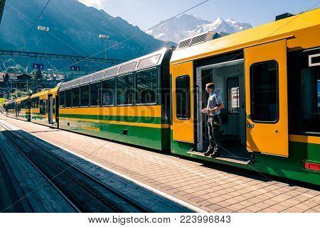 Wengen, Bernese Oberland, Switzerland - AUGUST 5, 2017 : Train of the Wengernalpbahn from Lauterbrunnen to Kleine Scheidegg in railway station in car-free village Wengen. Jungfrau mountain in the background.