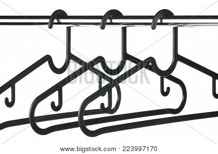 Three Black Plastic Coat Hangers On A Chrome Clothes Rail