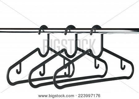 Three empty coat / clothes hangers on a clothes rail with a white background. Potential copy space above hangers.