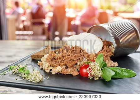 Pile of juicy food on black plate, closeup. Food and overturned can of plate, closeup.