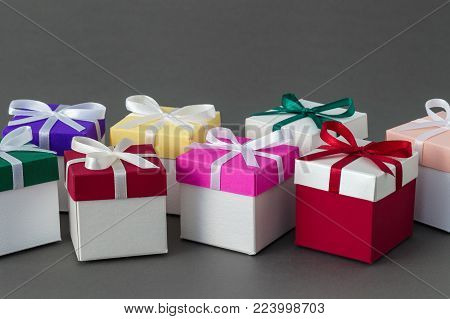 Several bright colorful gift boxes with ribbons on gray background. Copy space for text.