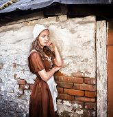sad woman in a rustic dress standing near old brick wall in old house feel lonely. Cinderella style. poster