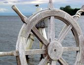 Ship wheel almost blocking the bird on a beautiful Harbor. poster