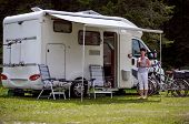 Woman is standing with a mug of coffee near the camper. Caravan car Vacation. Family vacation travel, holiday trip in motorhome RV poster
