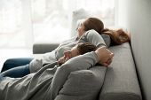 Relaxed couple asleep resting or having nap sitting on comfortable sofa enjoying daytime doze on weekend, calm carefree man and woman relaxing sleeping leaning on couch in cozy living room together poster