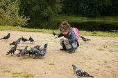 Girl is feeding pigeons in city garden summer poster