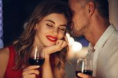 Young handsome man whisper to his gorgeous woman while have romantic dinner and drinking wine on valentines day poster