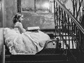 small girl kid with long blonde hair and pretty face in prom princess white dress with basket sitting near building glass big window on stairs reading book poster