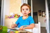 Mischievous baby blue color markers innocent face painted child . poster