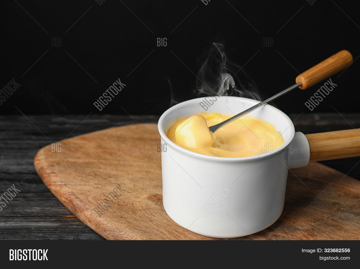 Pot Of Tasty Cheese Fondue And Fork With Bread On Black Wooden Table