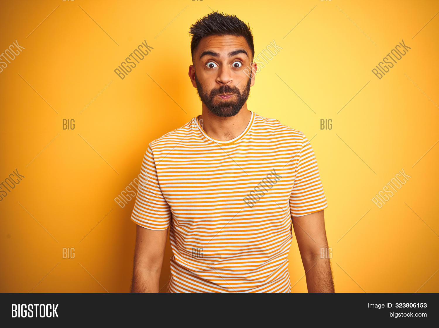 Young indian man wearing t-shirt standing over isolated yellow background puffing cheeks with funny face. Mouth inflated with air, crazy expression.