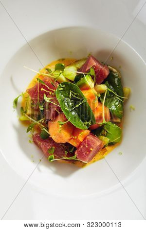 Exquisite serving tuna fillet and papaya salad in spicy sauce on white restaurant plate isolated. High cuisine restaurent dish with delicious yellowfin sashimi tartar in minimalist style topview
