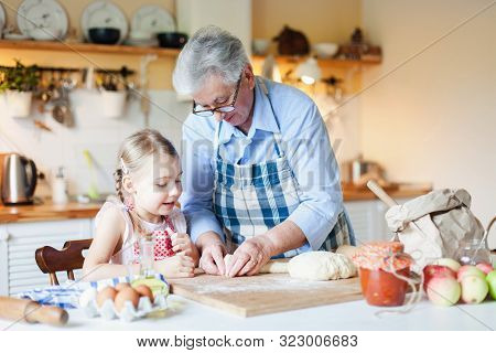 Grandmother Is Teaching Kid To Cook Pastries And Bread In Cozy Kitchen At Home. Senior Woman And Lit