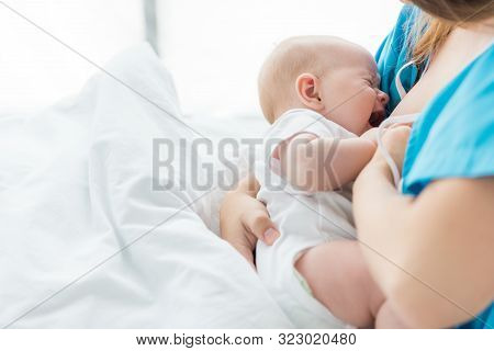 Cropped View Of Mother Breastfeeding Her Baby In Hospital
