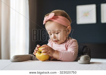 Nine-month-old Smiling Baby Girl In Pink Bandage On Her Head Sits At White Table In Highchair And Ho