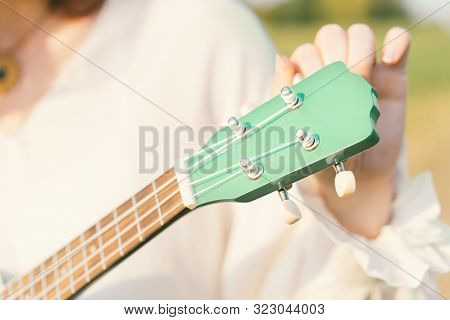 Woman Tuning Ukulele Strings. The Fretboard Of The Musical Instrument