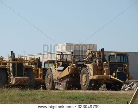Massive Earth Movers Set Ready To Begin Clearing Job Site..