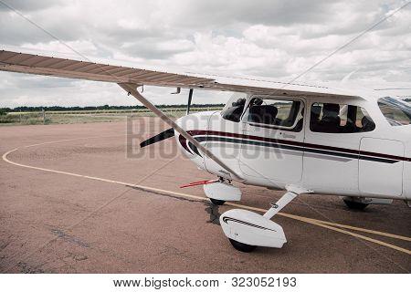 White Plane At Aerodrome Under Cloudy Overcast Sky