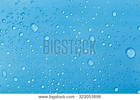 Rain Droplets On Blue Glass Background, Water Drops On Blue Glass.