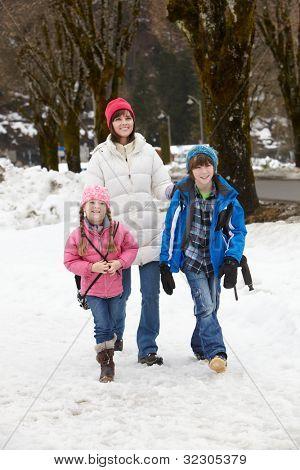 Mother Walking Two Children To School Along Snowy Street In Ski Resort
