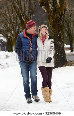 Couple Walking Along Snowy Street In Ski Resort